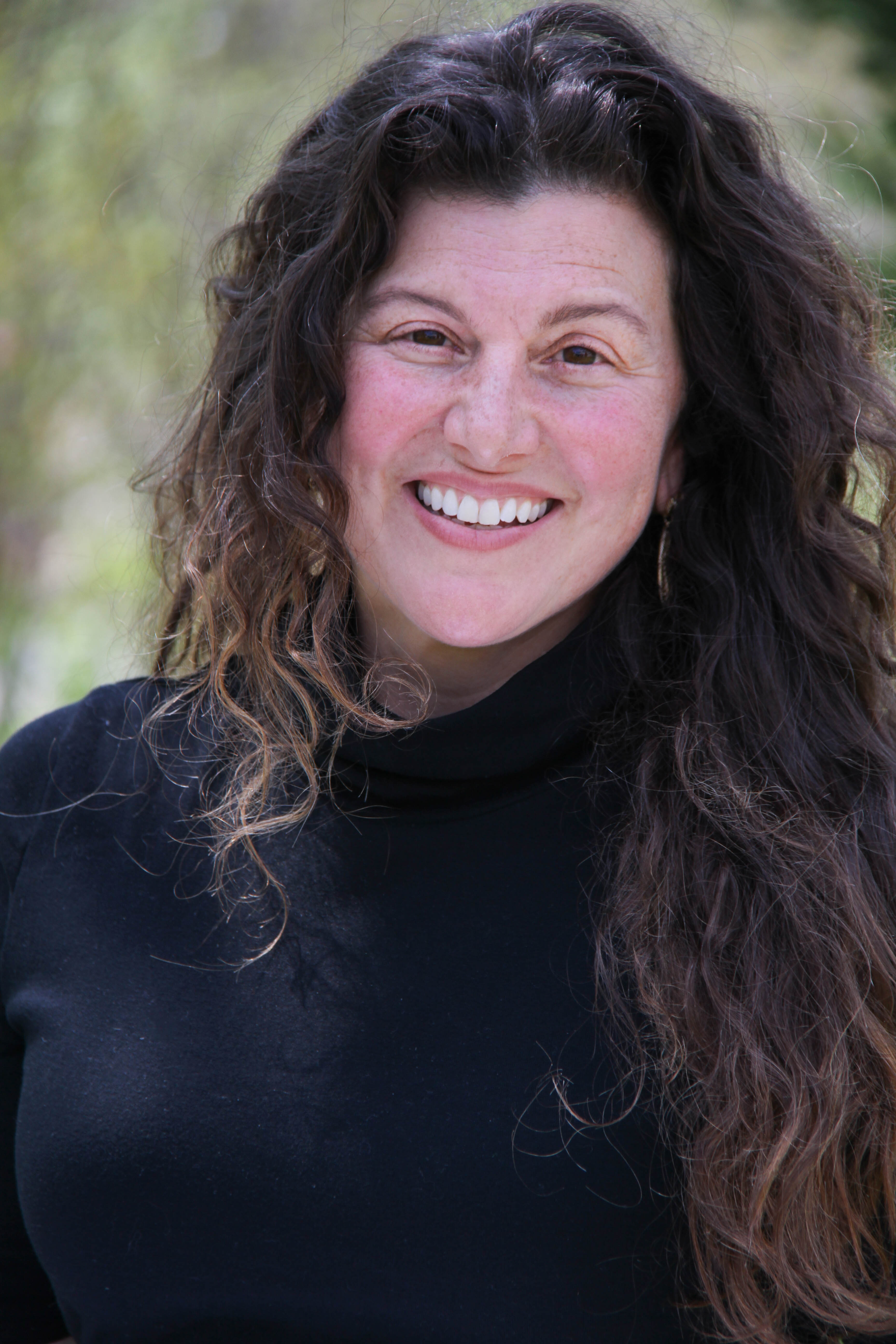 Lisa Condino smiles at the camera. Her long, brown, curly hair drapes and swirls around her face and over her shoulders. She wears a black sweater.