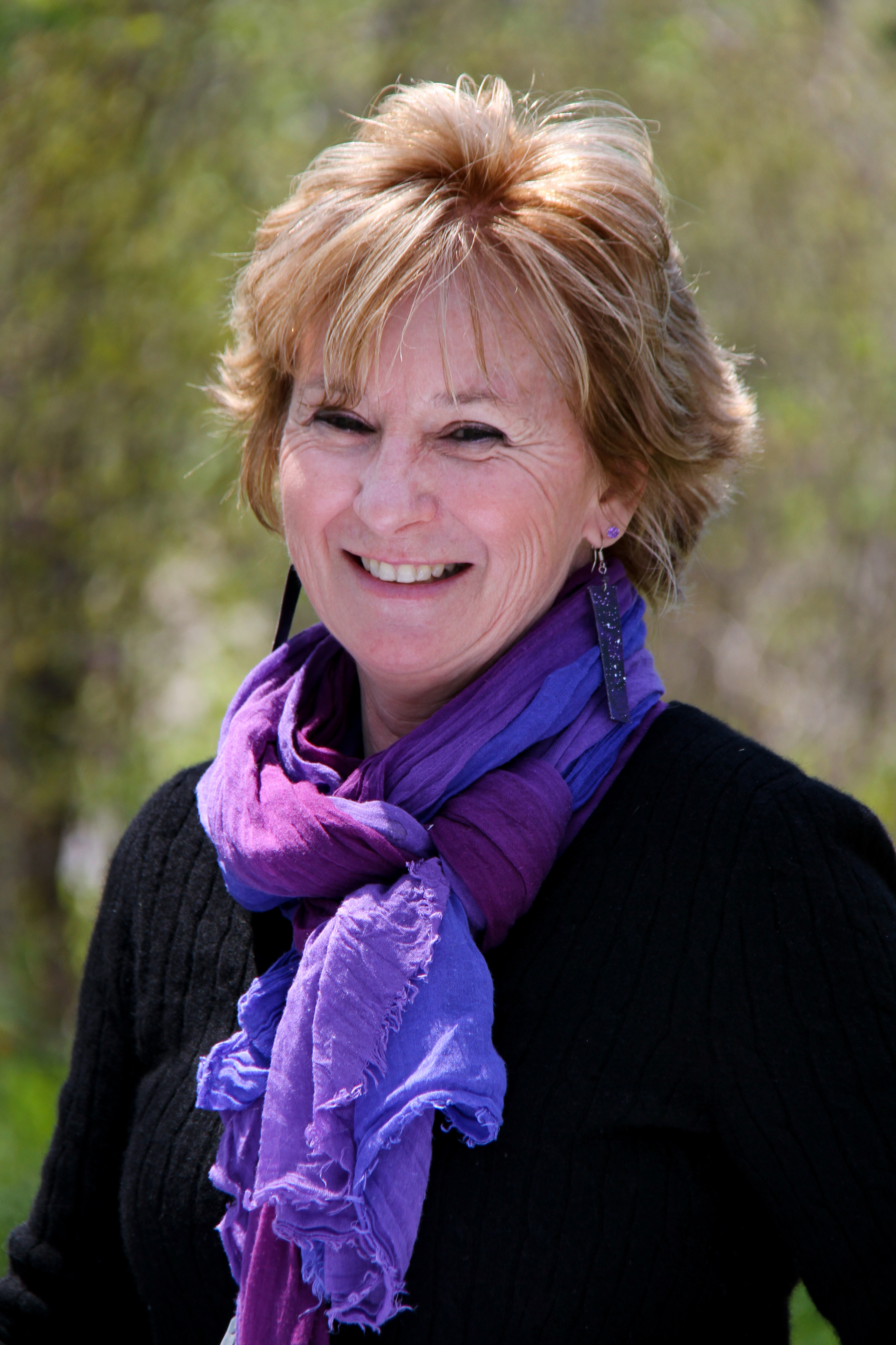Peggy Rainville smiles at the camera on a sunny day in front of a background of blurry green trees and. She wears a black sweater and bright purple scarf and wears long, rectangular, dangling earrings.
