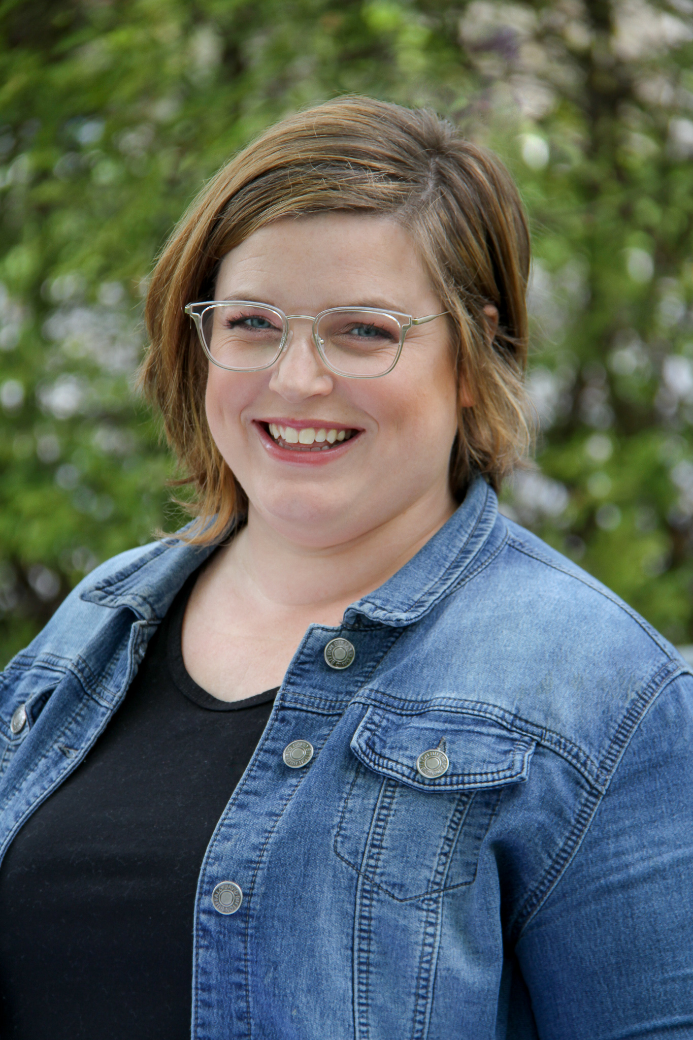 Katie Miller looks at the camera from behind clear-rimmed glasses, standing in front of a blurry background of green trees. She has short hair, and wears a denim jacket over a black t-shirt.