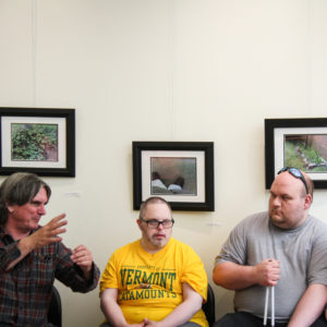 Three individuals are seated, facing the camera. They are engaged in conversation. The man at left gestures with his hand. They are seated in front of three framed photographs in black frames hanging on a white wall.