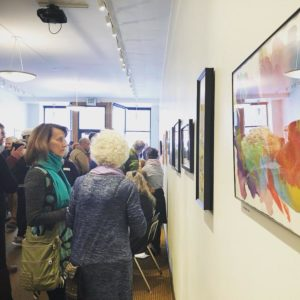 "A crowd gathers for the opening of ""FLOURISH."" At right, artworks line the wall. At left, individuals are engaged in conversation. A viewer in a teal scarf looks directly at the work on the wall."