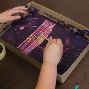 Two hands enter the frame, moving a brush inside a shallow cardboard box. There is a layer of thick purple paint that the artist scratches away, revealing abstract shapes of pink, blue, purple, and yellow.