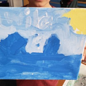 "A student holds up a piece of artwork, covering their face and body. The painting is on a canvas, made up varying shades of blue. A yellow circle resembling a sun rests in the upper right corner. In transparent white paint, the word ""wild"" reaches across the top third of the piece."