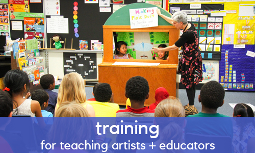 A group of students view a puppet show. A blue banner with white text reads: training for teaching artists and educators