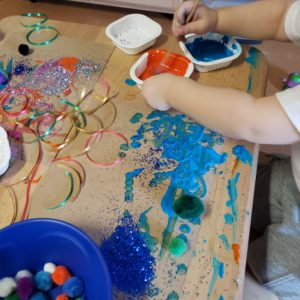 Viewed from above, a table is covered with brown paper and art supplies including ribbon, glitter, pom poms, and paint. A child's arms reach in from the upper right corner, dipping a brush in to a cup of orange paint.