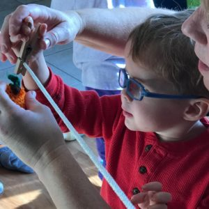In this closeup image, we see a young child in a red sweater and thick blue glasses pinning something to a clothesline with help from an adult.