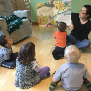 An adult is seated in front of a semi-circle of three children. She reads a book aloud to them. One child is close to the teacher, getting a closer view of the colorful pages.