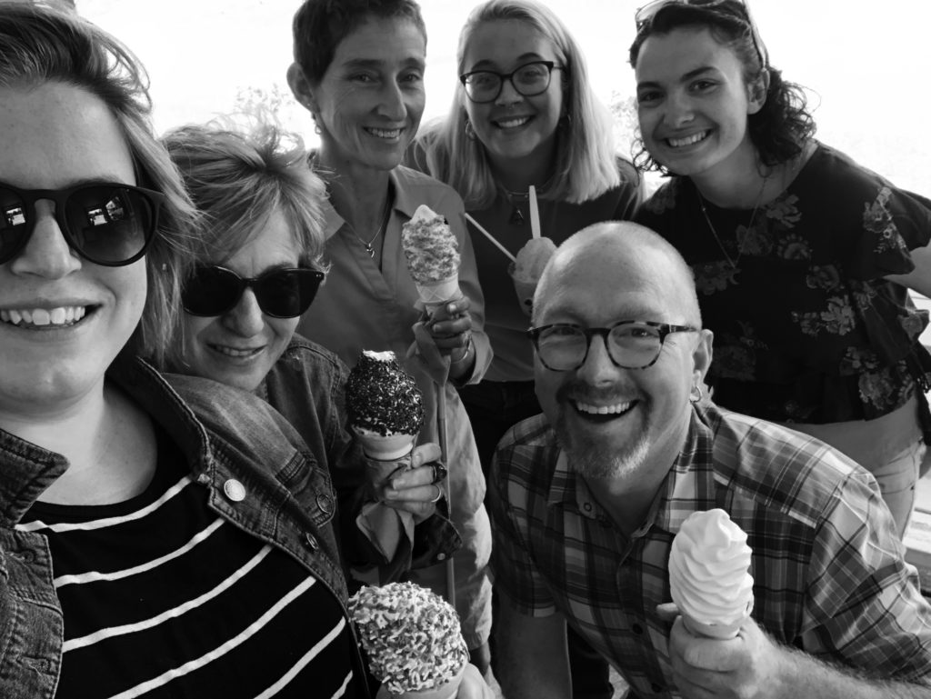The staff smile up at the camera, each one holding an ice cream cone or frozen treat, in this selfie-style portrait. From Left: Katie Miller, Peggy Rainville, Heidi Swevens, Rachel Paskavitz, Scott Robbins, and Emily Schulze.
