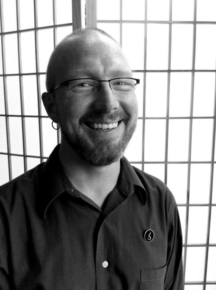In a black and white photograph, Scott is seated in slight profile although his eyes and smile are directed to the camera. His hair and beard are closely trimmed. He wears dark metal framed glasses, small hoop earrings, and a dark button down shirt that is open at the collar.