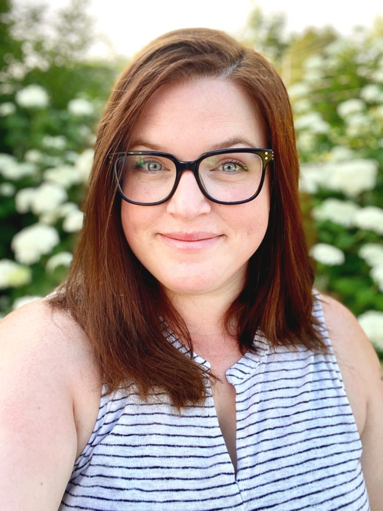 Katie Miller looks at the camera from behind black glasses. She has auburn hair and wears a white and black striped shirt. She stands in front of a bush of whit hydrangea blooms.