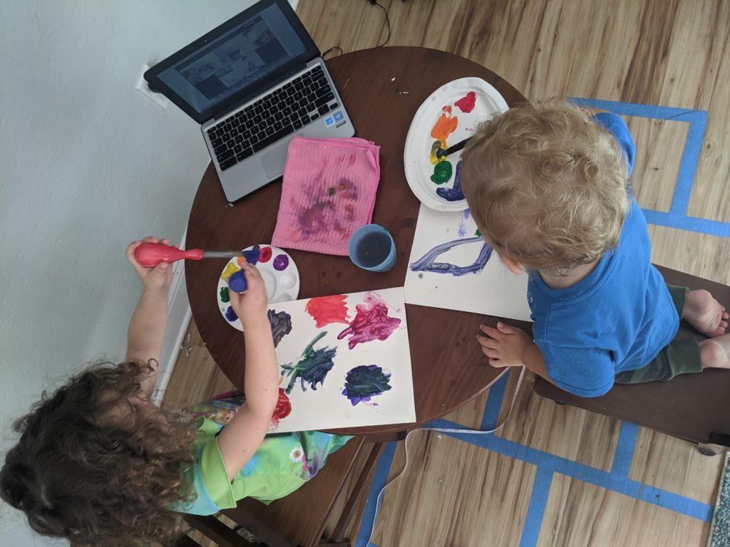 Two children sit at a table painting shapes on paper. Each child has a paint palette. There is a computer on the table with them, and on screen is a Zoom art class.