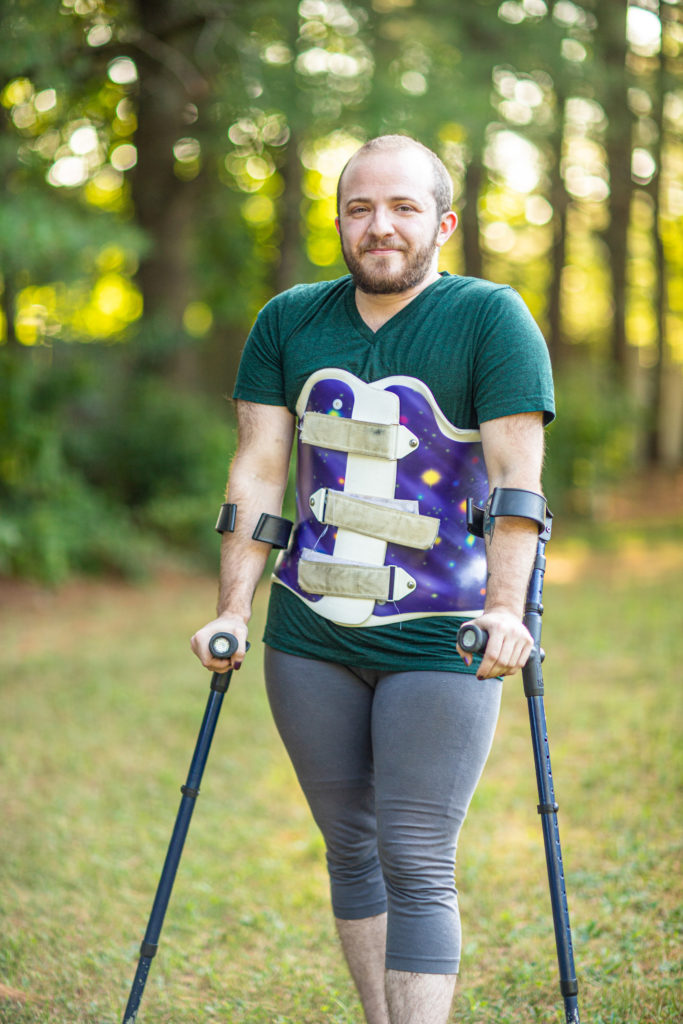 Toby, a white person with a short dark beard and a shaved head, standing casually with forearm crutches, in leggings, t-shirt, and a purple galaxy print back brace. They are outdoors with soft-focus golden-green trees behind them.