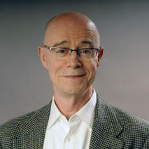 John Killacky stands in front of a gradientbackground that transitions from dark to light gray. He has pale skin, blue eyes, and is balding. He wears a pair of gray and clear glasses and a gray, checked blazer over a white button-down shirt.